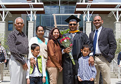 Graduate with family in front of the Campus Center
