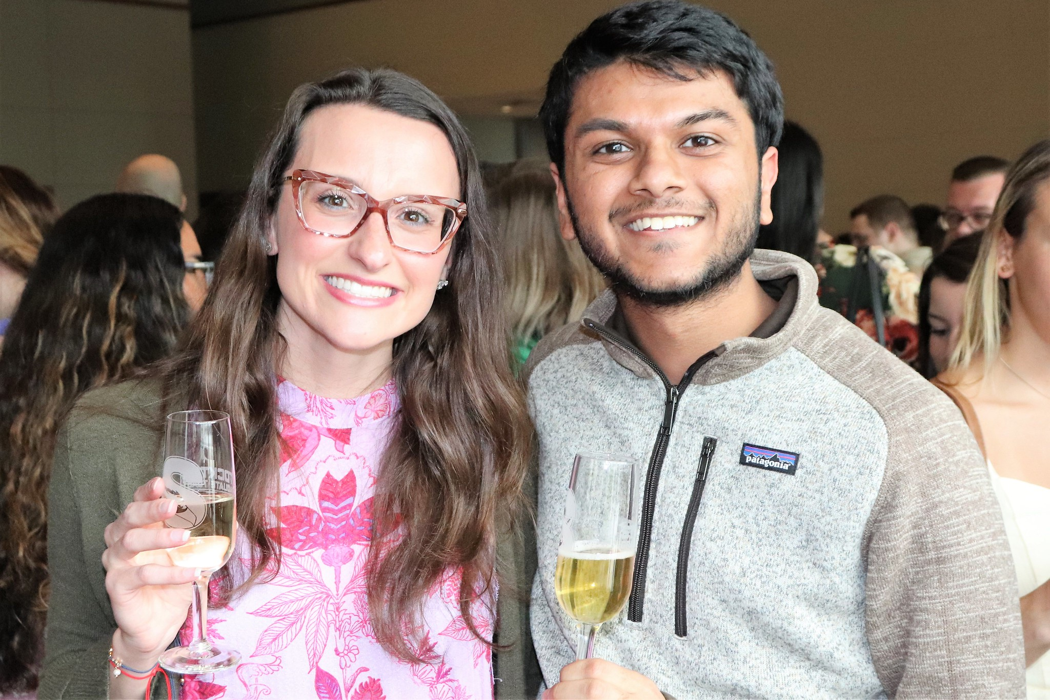 woman and man smiling with toasting glasses