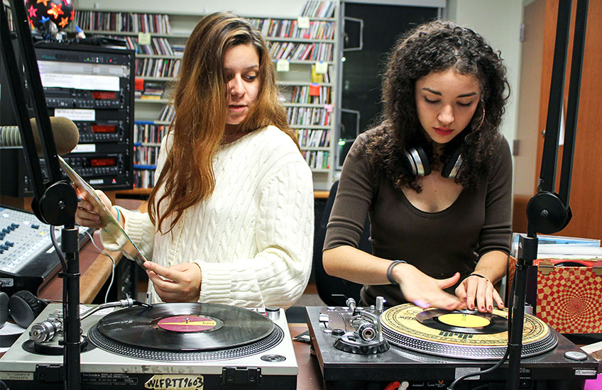 two girls working with DJ equipment