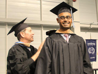 Amar Shah is congratulated on earning his MBA by Business Studies Professor Michael Busler at the Master's and Doctoral Commencement held May 10.