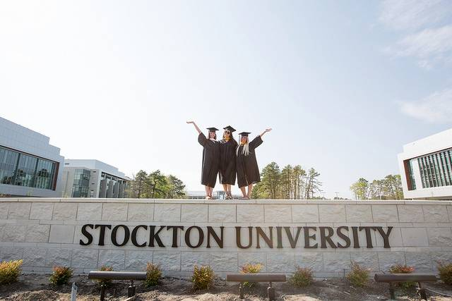 Girls standing on stone wall in graduation gowns
